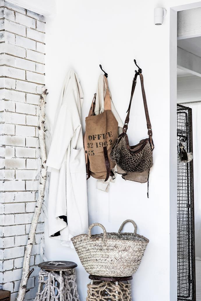 """I wanted the entry to our home to be simple, easy and practical,"" Virgine says. Hooks from Mona Market in Paris hold vintage bags, while a Mamapapa basket perches on one of the stools by extreme knitter Jacqui Fink."