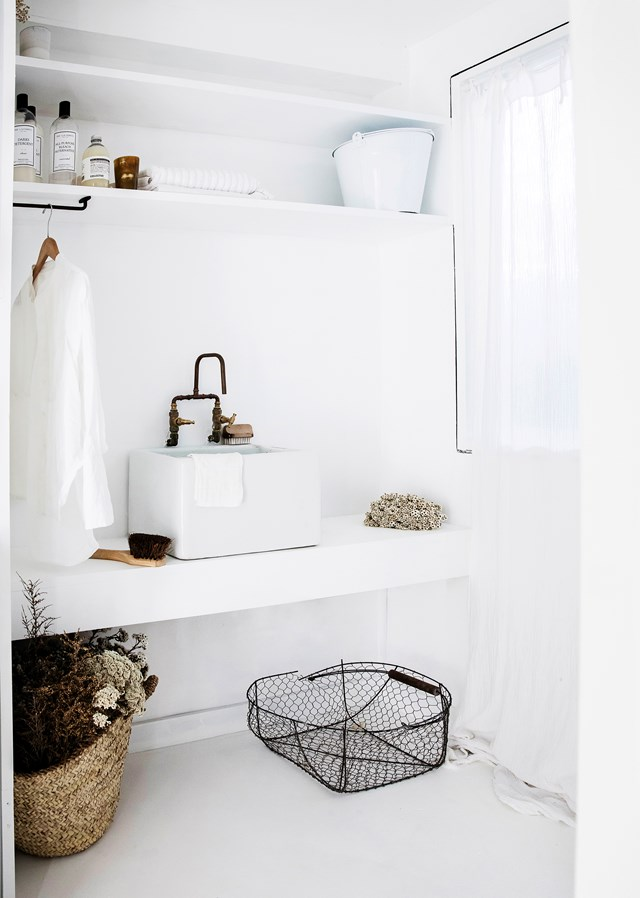With its fresh white palette, concrete flooring, custom shelving, enamel basin and vintage tapware, this is one laundry that we would happily visit every day! Photo: Maree Homer | Styling: Kristin Rawson | Story: *real living*