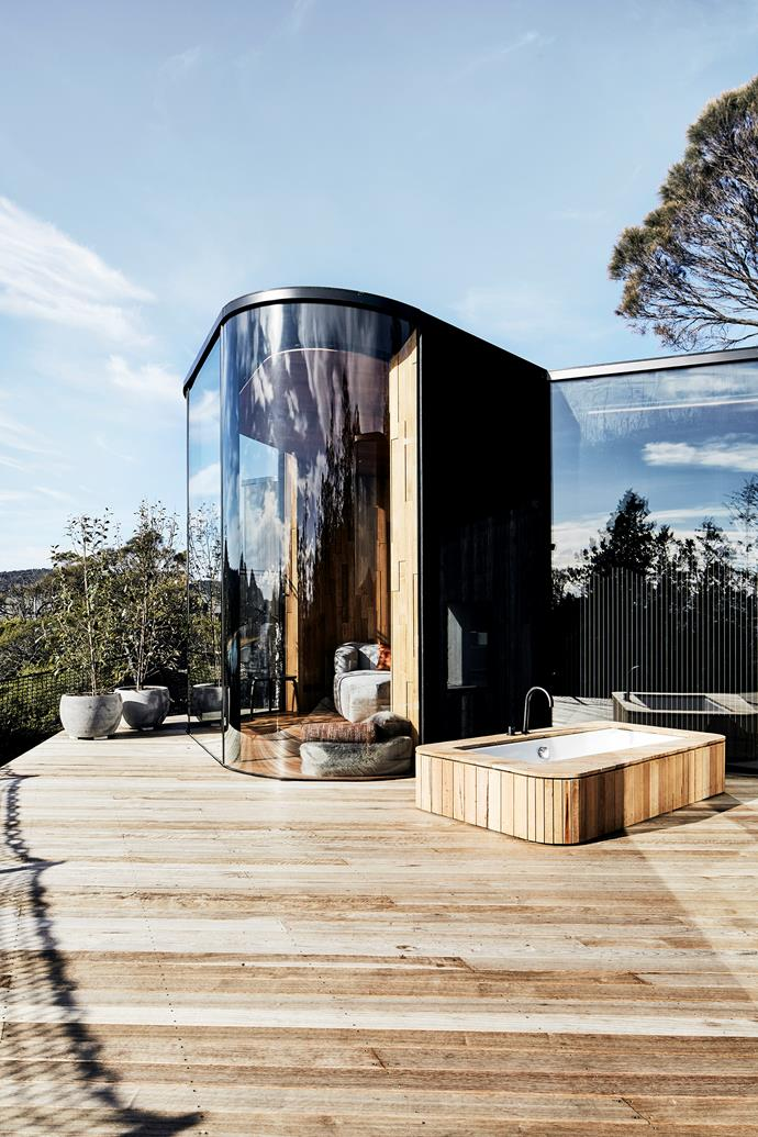 """Bask in the breathtaking view from the bath or slide the pull-apart """"Pebble"""" sofa onto the grey gum timber deck."""