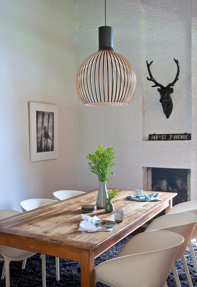 **Dining** A timber pendant light hangs over a timber dining table paired with a lush navy rug and white dining chairs.