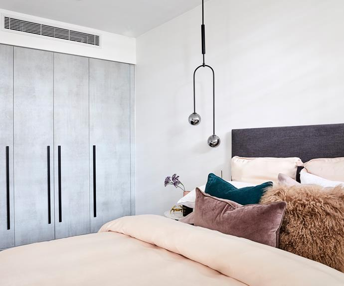 **Courtney and Hans** The mix of textures on the bed plays well with the industrial concrete finish of the wardrobe.