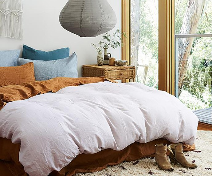 Bed with linen sheets and linen lantern