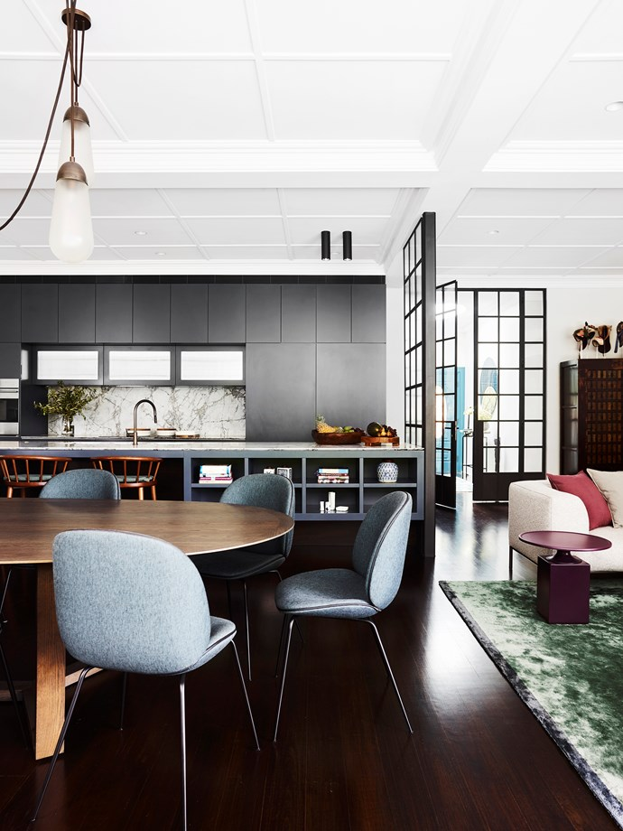In the dining area, Lowe Furniture 'Atticus' oval table in American oak and bar stools from Hub. Gubi 'Beetle' chairs from Cult. Custom bamboo silk rug from Robyn Cosgrove.