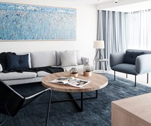Coastal style living room with blue artwork, timber furniture and grey lounge chairs