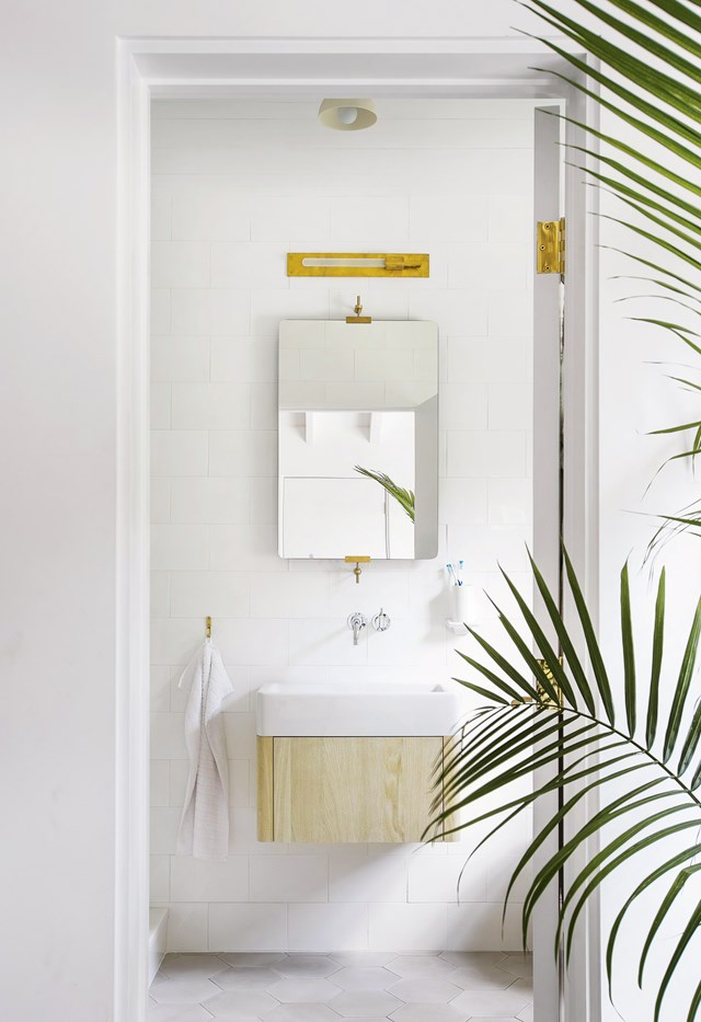 "Even just a glimpse of this bathroom in a [Hamptons meets Scandi holiday home](https://www.homestolove.com.au/hamptons-meets-scandi-in-this-holiday-home-18834|target=""_blank"") gives us major relaxtion vibes. The white palette has been punctuated with touches of brass and a floating blonde timber vanity. *Photo: Matthew Williams*"