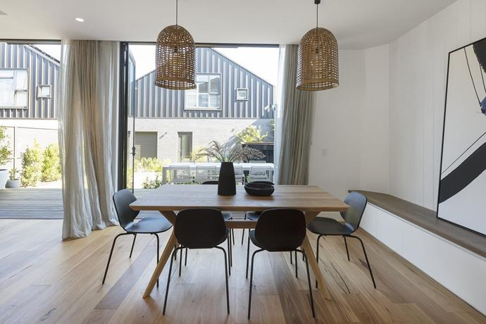 """In the [dining room](https://www.homestolove.com.au/dining-rooms-5533 target=""""_blank""""), gone are the upholstered chairs and concrete table chosen by Sticks and Wombat, and in their place is a sleek black and timber setting which opens up the space. *Photo: Domain*"""