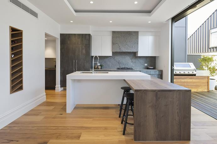 """The modern kitchen features a custom timber wine-rack and [Caesarstone countertops](https://www.homestolove.com.au/durable-engineered-stone-kitchen-benchtops-18823 target=""""_blank""""). *Photo: Domain*"""