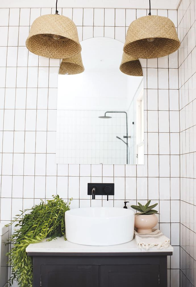"""**DIY tip** """"Baskets and raffia are some of my favourite styling and DIY elements,"""" says Geneva. """"For the bathrooms, I removed the handles from IKEA baskets, cut a hole in the bottom and slid them onto the light fixtures."""" 'Avalon' wall tiles, [Tile Cloud](https://tilecloud.com.au/ target=""""_blank"""" rel=""""nofollow""""). Vanity, vintage sewing table painted in Haymes paint in Intimacy, [Haymes Paint](http://www.haymespaint.com.au/ target=""""_blank"""" rel=""""nofollow""""). Mondella 'Rumba' basin & tapware, [Bunnings](https://www.bunnings.com.au/ target=""""_blank"""" rel=""""nofollow"""")."""