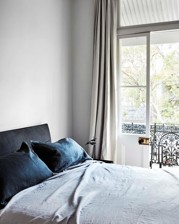 One of the home's bedrooms enjoys plenty of light filtering in through a set of French doors.