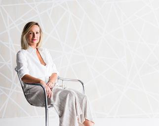 Sarah Ellison sitting in a chair in front of geometric wallpaper