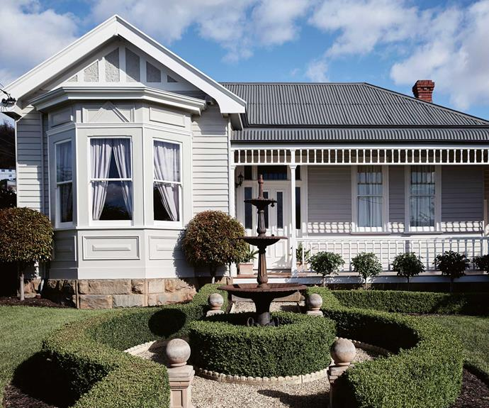 """A manicured formal garden complements the home's facade, painted in [Dulux White](https://www.homestolove.com.au/dulux-white-paint-colours-5396