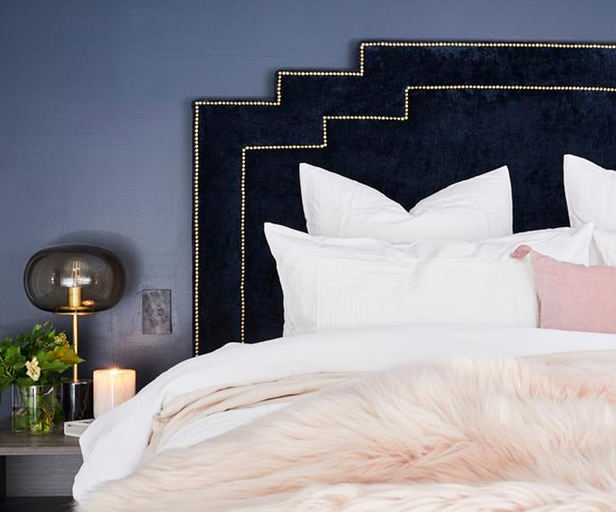 Bed styled with white and pink linen and statement navy bedhead