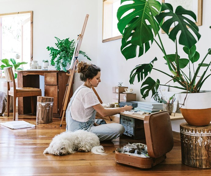 The artist lives here with her marine biologist partner Curtis, and cites the lack of a phone line and wifi as a great catalyst for work and study. Recycled stumps, decorated by Brigitte, are repurposed as stools and sidetables around her workspace.    | Photo: Marnie Hawson