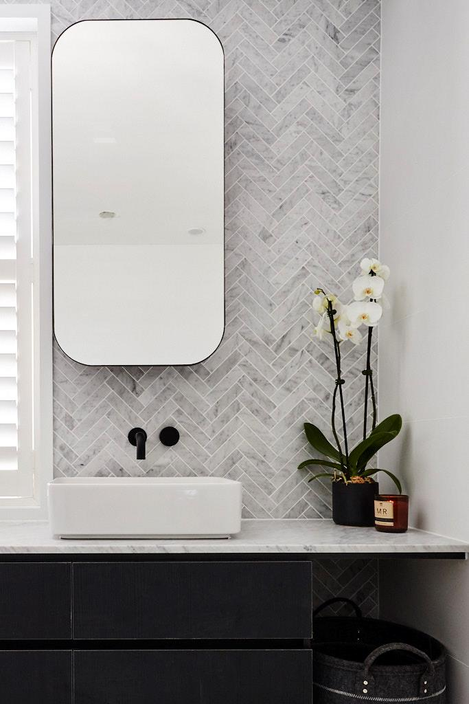 In their ensuite, Kerrie and Spence spent big on the marble herringbone splashback - and let simple finishes and a well-designed layout take care of the rest.
