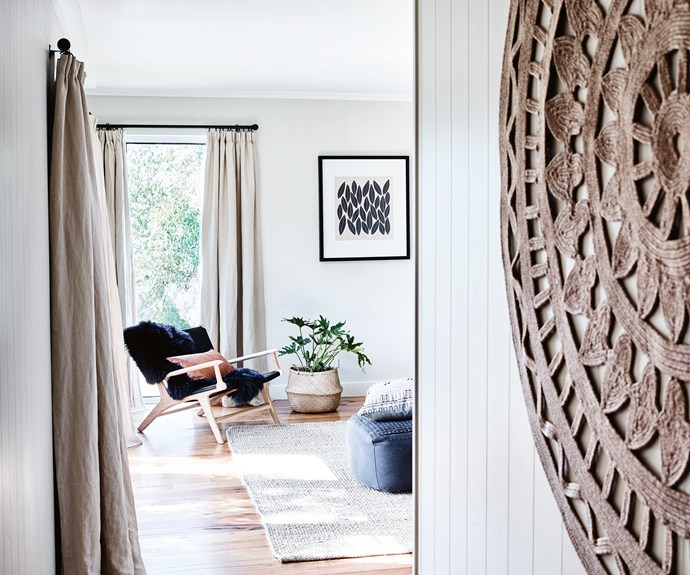 One of the couple's guest suites features a floor rug from [Freedom Furniture](https://www.freedom.com.au/) as a wall hanging. Along the wall is an 'Abundance' print by [Designer Boys Art](https://www.designerboyscollections.com/landing/). The interior is painted in Dulux Half Duck and the curtains are from [Linen Shed](https://www.linenshed.com.au/), while the 'Genevieve' pouf is from [Adairs](https://www.adairs.com.au/). The 'Marvin' chair is from [The Belle Bright Project](http://www.thebellebrightproject.com.au/) — the company also worked on the interior design of the guest suites. | Photo: Mark Roper