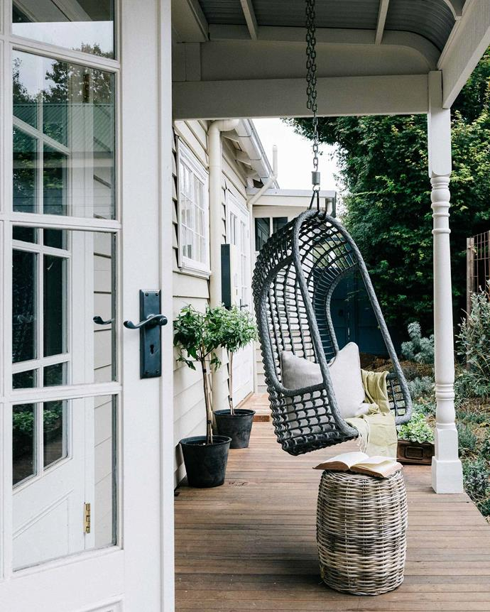 """A hanging chair from [HK Living](http://hkliving.com.au/ target=""""_blank"""" rel=""""nofollow"""") and wicker stool from [Early Settler](https://www.earlysettler.com.au/ target=""""_blank"""" rel=""""nofollow"""") on the verandah. *Photography: Marnie Hawson*"""