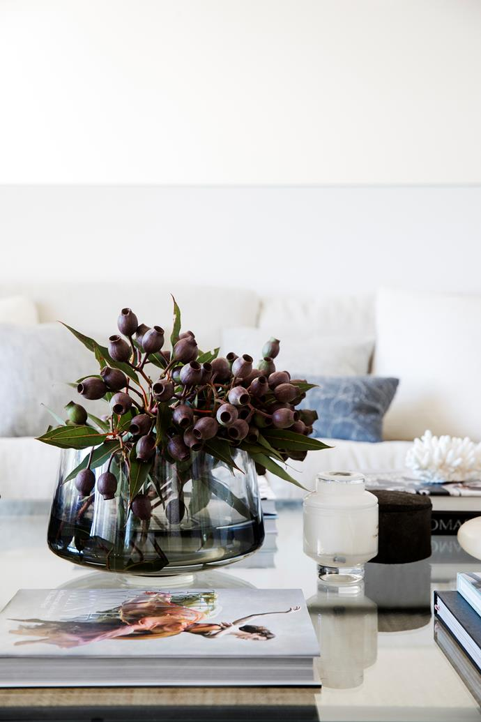 Dark-coloured gumnuts in a smoked-glass vessel are the perfect foil for the light living space. Vase, Coco Republic.