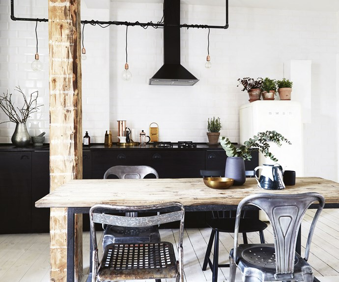**Kitchen and dining area** The dining table is at the centre of the combined living area and kitchen. The wall behind the black IKEA kitchen is clad with classic white subway tiles, and the exposed pipes play to the industrial style.