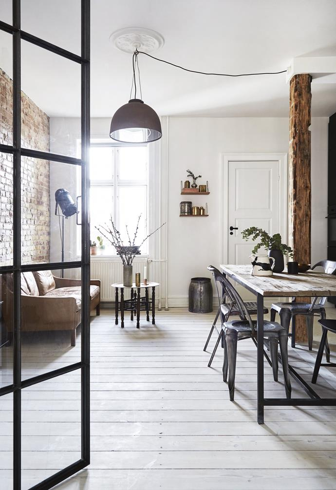 **Living and dining area** Looking from the bedroom, the raw brick wall, exposed timber column and industrial lamps give the apartment some of the old-school New York style Sofie dreamt about.