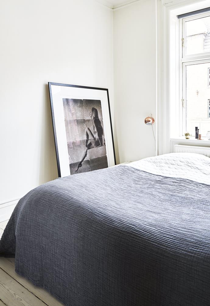 """**Bedroom** Sofie and Mikael's room is simply furnished with a built-in wardrobe on the other side of the bed. Artwork: Photograph from *Limit To Your Love* series by [Jacob Gils](http://jacobgils.com/
