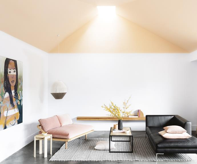 """Soft peach defines the living area, which is crowned by a skylight. """"We find sneaky ways of getting in as much light as possible,"""" says architect [Monique Woodward.](http://www.wowowa.com.au/) A [Pop & Scott](https://www.popandscott.com/) pendant light drops to the side. Touches of grey and black balance the warm peach ceiling in [Dulux](http://www.dulux.com.au) Curtsy and pink velvet daybed from [Pop & Scott](https://www.popandscott.com/). Photography by Martina Gemmola. Styling by Ruth Welsby Photographer: Martina Gemmola, Stylist: Ruth Welsby"""