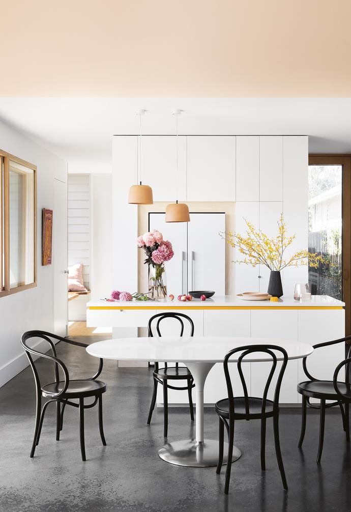 This home's colour composition is at its best in the kitchen: yellow edging tones with pendant lights from [Anchor Cermics](http://anchorceramics.com/) and touches of plywood. The black mirrored splashback ties into the family's black leather sofa and is echoed with [Thonet](http://www.thonet.com.au/) dining chairs and the polished concrete floor. Photography by Martina Gemmola. Styling by Ruth Welsby. Photographer: Martina Gemmola, Stylist: Ruth Welsby