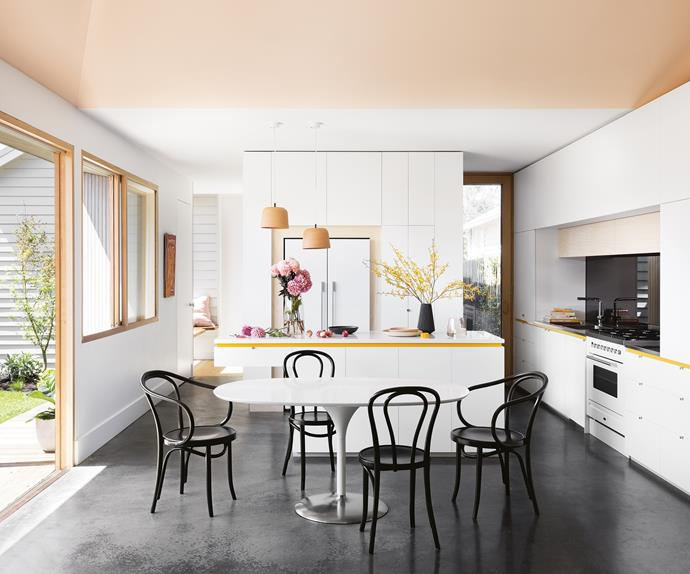 """This home's colour composition is at its best in the kitchen: yellow edging tones with pendant lights from <a href=""""http://anchorceramics.com/"""" rel=""""noopener"""" target=""""_blank"""">Anchor Cermics</a> and touches of plywood. The black mirrored splashback ties into the family's black leather sofa and is echoed with <a href=""""http://www.thonet.com.au/"""" rel=""""noopener"""" target=""""_blank"""">Thonet</a> dining chairs and the polished concrete floor. Photography by Martina Gemmola. Styling by Ruth Welsby."""