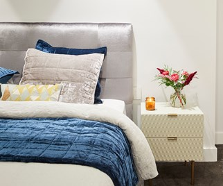 Bed with grey and navy velvet linen and bedside table