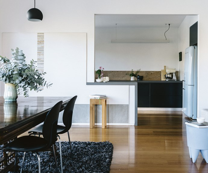 Josephine's late grandfather made the vase on the couple's dining table, which is from Pegasus Antiques in Geelong. The pendant light is from Hub and the blue stool from Space Furniture ties in nicely with the Smeg fridge.  | Photo: Marnie Hawson
