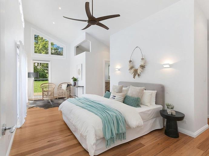 This breezy coastal bedroom feels larger than life with its high ceilings, large windows and access to the outdoors. *Photo: Domain*