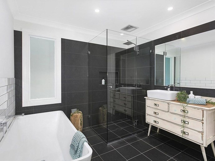 While were not sure about the black tiles in a coastal bathroom, this space is big enough for a family to use comfortably. *Photo: Domain*