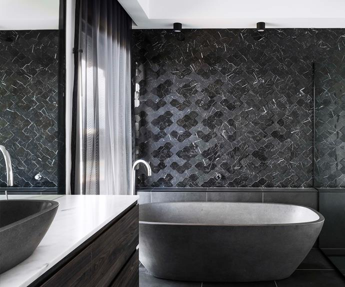 A freestanding stone bathtub in dark, industrial minimalist bathroom