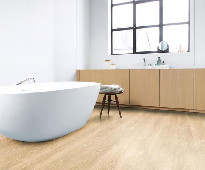 Freestanding bath tub in a bathroom with timber look floors