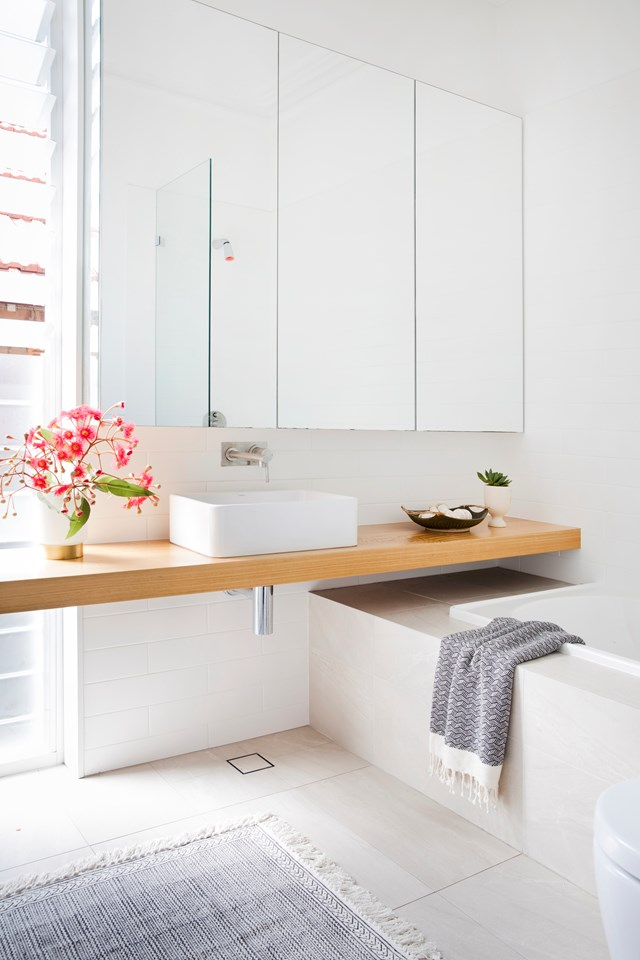 """A wall-to-wall timber bench running perpendicular to an inset tub means every inch of space is maximised in the main bathroom of this [renovated Federation home in Sydney](https://www.homestolove.com.au/contemporary-renovation-federation-style-home-in-sydney-18993