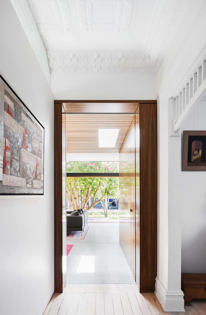 In the hall, a spotted-gum door frame/storage wall eases the transition between old and new.