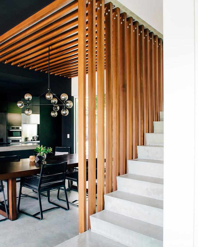 The dining room welcomes in light from both sides to illuminate its dark timber finish. The timber batons that pave the ceiling form a balustrade to the stairway. | *Photo: Christopher Morrison*