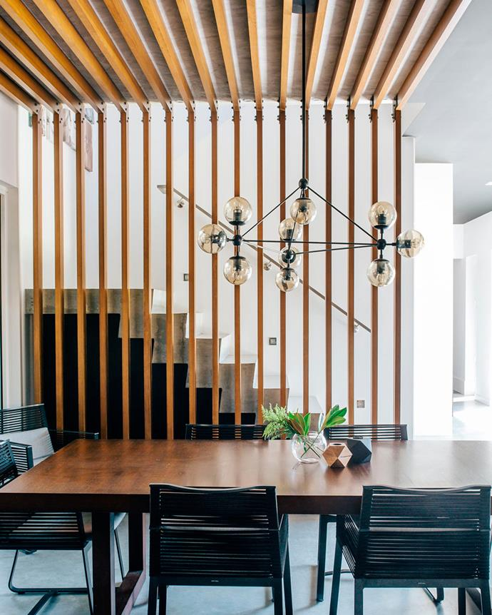 "The dining room is bordered by timber batons, part of the home's signature pared back aesthetic. The owner imagined a traditional front with Victorian proportions, but with a surprise out back to take advantage of the property's location on a corner site. This ""stripped back, contemporary version of a cottage"" is comprised of six bedrooms (including a studio over the garage, a study room and a playroom), and two living areas where the family dine and lounge.