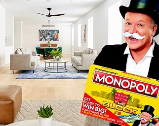 Scott Cam dressed as Mr Monopoly holding Monopoly The Block Special Edition board game