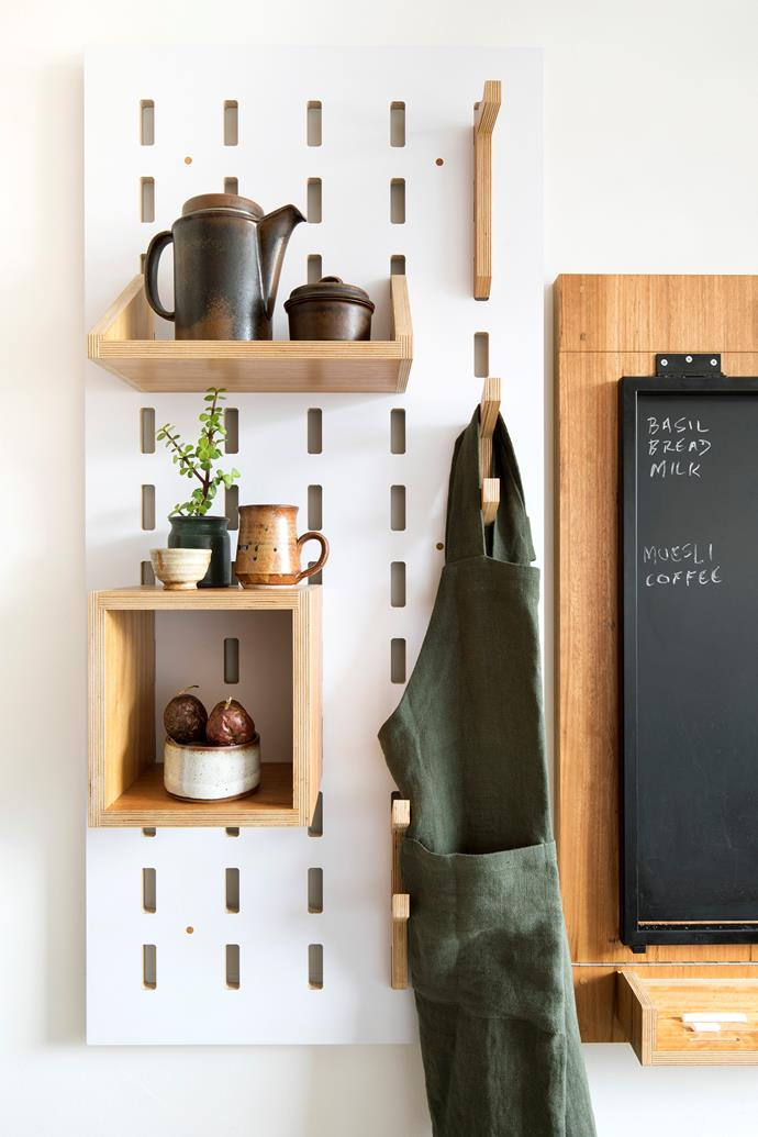 The wall-mounted modular shelving units are made from 1200x600mm sheets of white-faced plywood with laser-cut slots. Shelves and storage boxes hook onto the slots and lock into place. Black terracotta pan, fruit bowl and apron, all from The Hub General Store. *Photo:* Shania Shegedyn