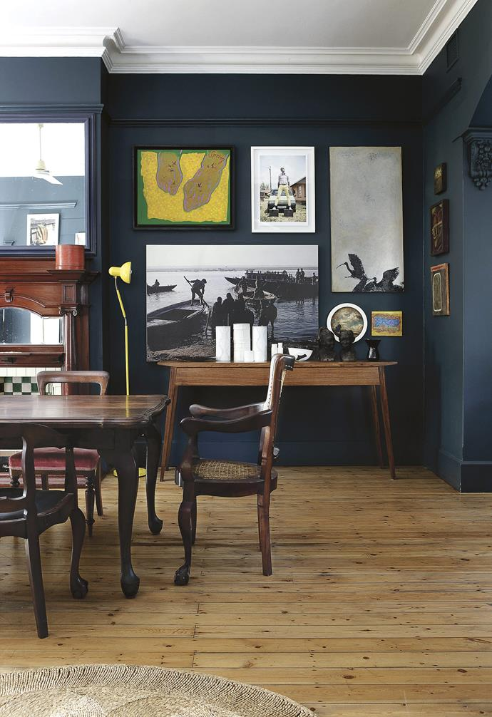**Dining area** Dark timber and walls create a moody atmosphere. Rick inherited the 10-seater Queen Anne table from his mother. His 'Pretty Filly' sideboard sits below a wall of artwork. Artwork: (clockwise from top left) painting by Andrew Verster, Photograph by Chris Saunders, *Hadedas* by Bronwen Vaughan-Evans, (small square) painting by Andrew Verster, (small circle) painting by Grace Kotze, Photograph by Angela Shaw.
