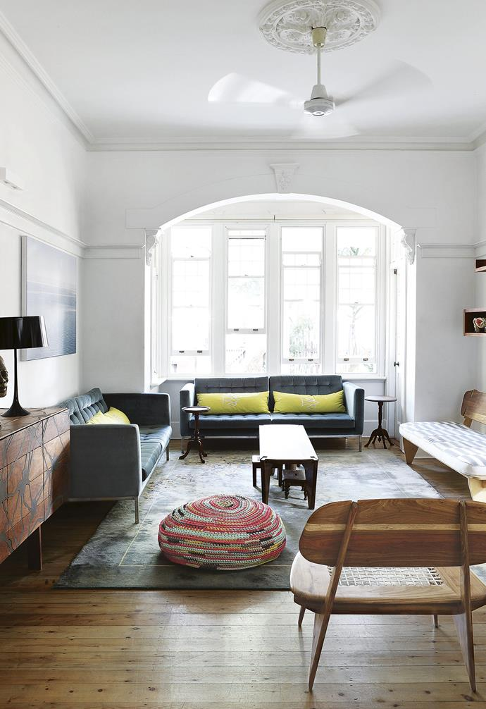 **Living area** The huge bay window floods this space with light. The floor cushion is one of Angela's designs, while the timber 'Slow' chairs and graphic cabinet are Rick's. Artwork: Photograph by Angela Shaw