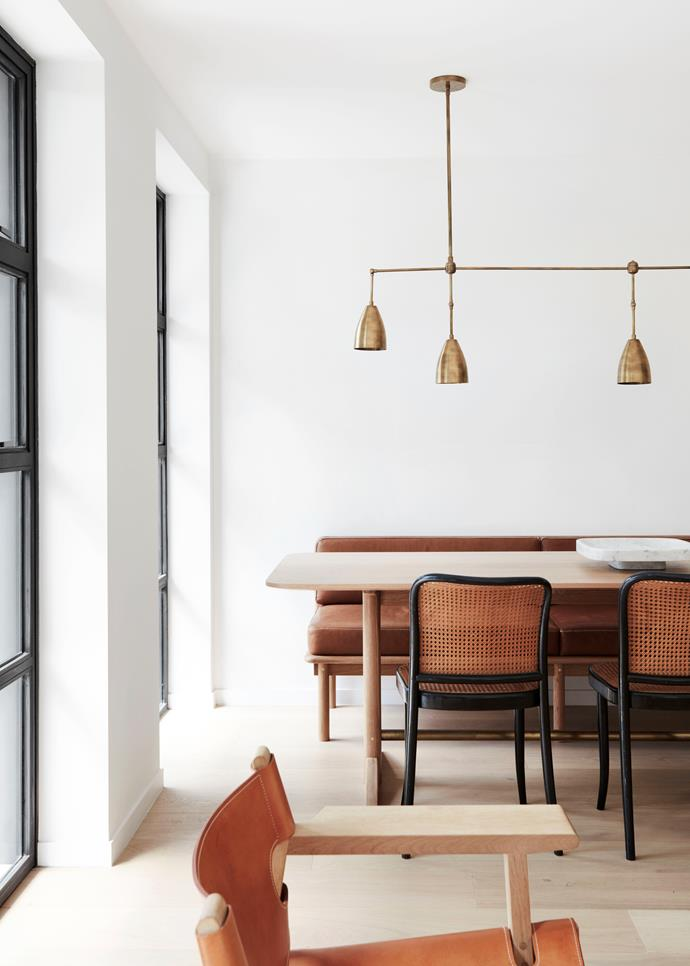 'Twig 5' pendant from Apparatus Studio hangs over the dining table and banquette designed and built by Jonathan West. Thonet chairs from The Vault.