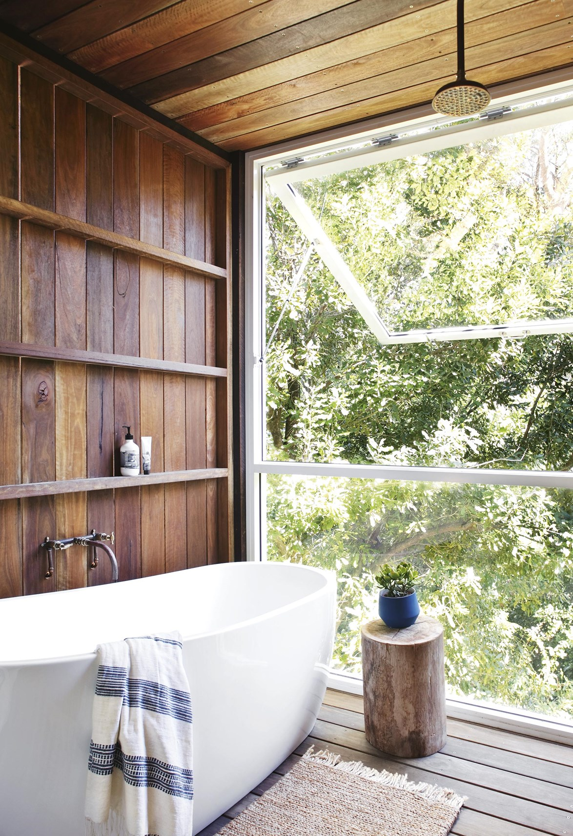 "An ingenious [gas-strut window](https://www.homestolove.com.au/renovation-and-design-trends-5801|target=""_blank"") extends this timber-clad bathroom into the great outdoors. *Photo: Anastasia Kariofyllidis / Styling: Simon Barter / Story: Inside Out*"