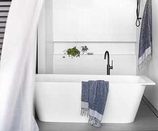 White freestanding bathtub in white coastal bathroom