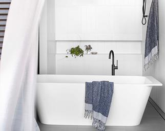 White freestanding bathtub in white coastal bathroom