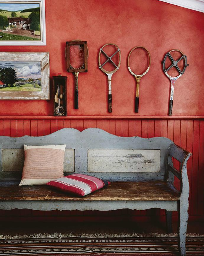"Annie applied red glaze over a salmon colour that the painters had used by mistake in the pool room. Old racquets hang alongside paintings by Annie's father (top) and Rachel Roxburgh (bottom). Annie bought the bench from [an antiques store](https://www.homestolove.com.au/how-to-decorate-with-vintage-second-hand-finds-4673|target=""_blank"") 20 years ago."