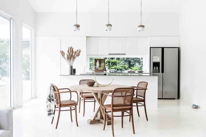 "The living space, which includes the kitchen and dining areas, is Lara's favourite part of her home. ""I love that it's so open with lots of light and high ceilings and that it's very simple, with three pendants and a window splashback as the focus."""