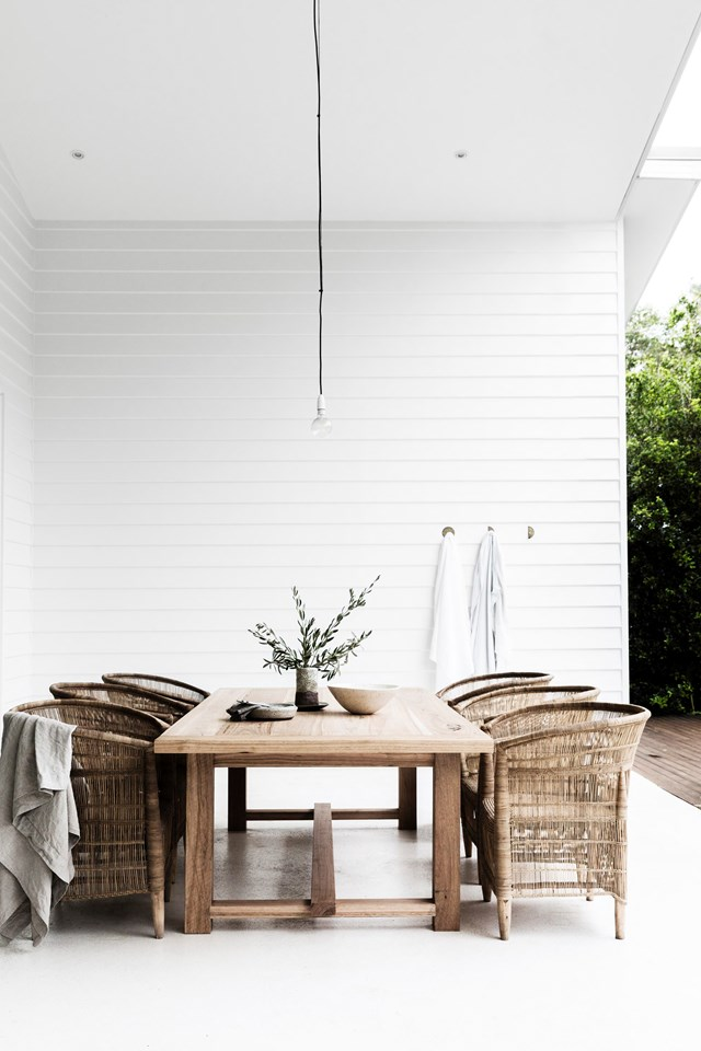 "This [Byron Bay home](https://www.homestolove.com.au/a-byron-bay-home-filled-with-handcrafted-finds-19045|target=""_blank"") favours white inside and out. To maximise natural light, concrete floors have been painted white and large windows left curtainless, except for the bedrooms. Timber furniture and textured rugs add warmth throughout. *Photo:* Maree Homer"