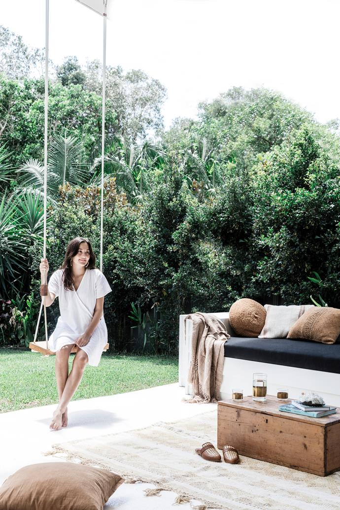 """I think Australian homes really make the most of outdoor living,"" Lara says, pictured on a swing from Pop & Scott. The couple painted the original grey exterior white and had a day bed custom-built in the outdoor sitting area with storage under the seats – a practical addition that's perfect for lazing about in the afternoon sun."