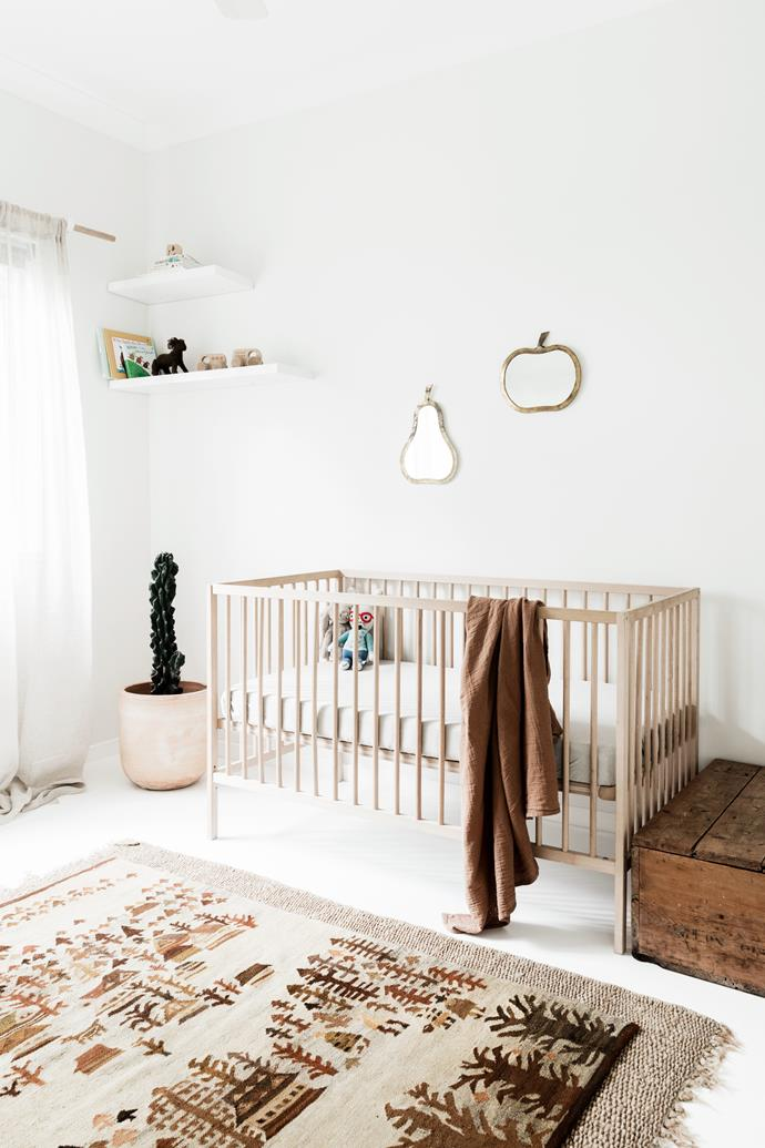 "The neutral colour palette flows into the nursery, which is decorated with a vintage rug and fruit-shaped mirrors from [Tigmi Trading](https://tigmitrading.com/|target=""_blank""